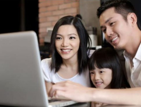 Picture of a family of three sitting in front of a laptop smiling