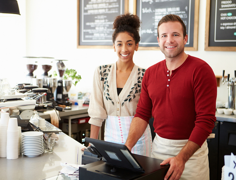 A woman and man business owners standing at their register.