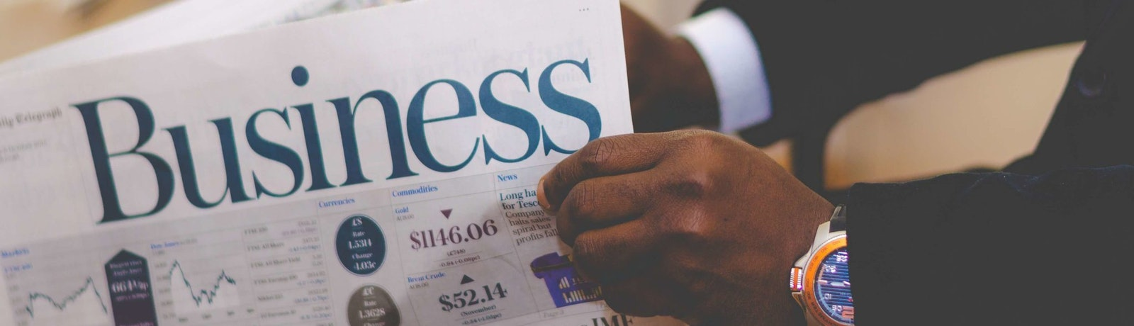 a pair hands holding the business section of the newspaper